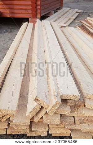Boards In Stack Against Wooden House Under Construction