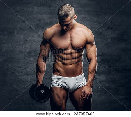 Sexy Shirtless Muscular Male In White Panties Holds Dumbbell Isolated With Contrast Illumination On