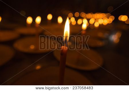 Candles In The Dark Blur Background,close Up Light Candle Flame,yellow Burning Candle On Dark Tone B