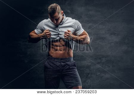 Young Athletic Male In White Shirt Shows Six Pack Abs.