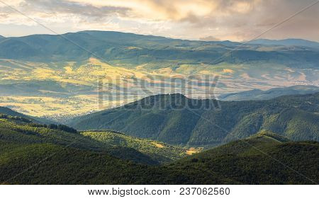Sun Lit Valley In Afternoon. Beautiful Mountainous Landscape And Cloudy Sky In Golden Light. Lovely