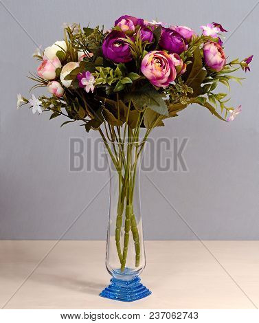 Still Life With Artificial Flowers Of Roses And Carnations Of Red, Purple, Yellow And White And Gree