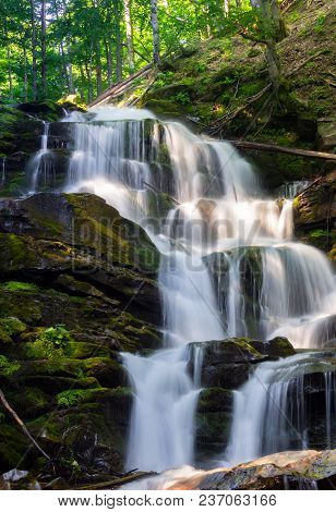Cascades Of Big Waterfall In Forest. Beautiful Summer Scenery At Sunrise. Beams Of Light On Water Sp