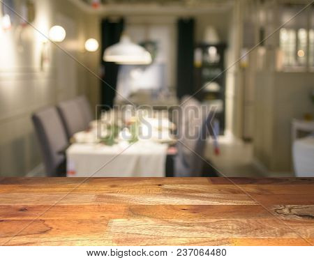 Empty Wooden Display Table Top Front With Blurred Dining Room On Background. Mockup.