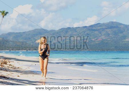 Young Beautiful Girl In Black Swimwear Jogging On The Blue Beach
