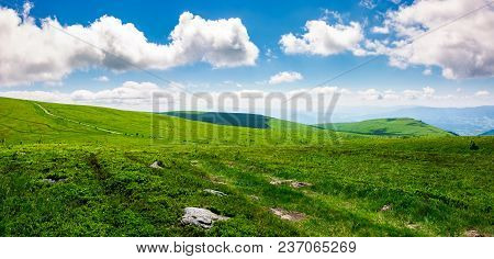Beautiful Panoramic Mountainous Landscape. Lovely Summer Scenery Of Grassy Hills Under The  Blue Sky