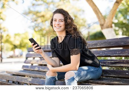 Stylish Young Woman Sitting On A Park Bench With A Smart Phone