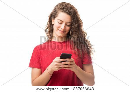 Pretty Young Caucasian Girl Using Her Mobile Phone While Standing Against White Background