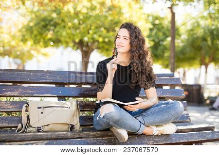 Cute Young Woman Sitting Outside In A Park Bench And Thinking While Writing In A Journal