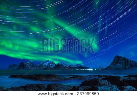 Northern Lights, Aurora Borealis Shining Green In Night Starry Sky With Star Tracks At Winter Lofote