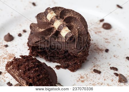 Chocolate Cupcake On White Plate With Fork, Dusted With Cocoa Powder And Chocolate Sprinkles, Half E