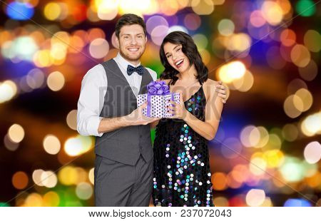 valentines day, birthday and holidays concept - happy couple with gift box at party over festive lights background