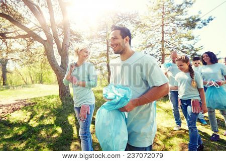 volunteering, charity, people and ecology concept - happy young volunteers with garbage bags walking outdoors