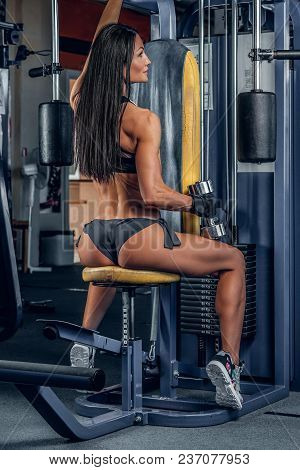 Brunette Sexy Female From The Back Doing Workout On Multi Action Exercising Machine In A Gym Club.