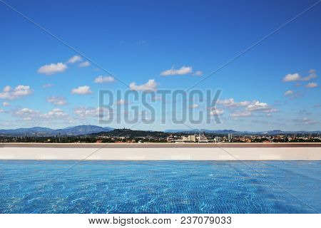 Luxury Swimming Pool On Rooftop. Blue Sky With Clouds And Mountain Landscape On Background. Panorami