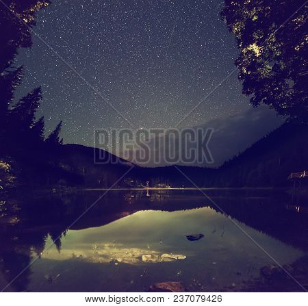 Mountain Lake Synevir At Night With Starry Sky And Reflections In The Water. Natural Outddors Travel