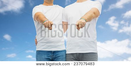 lgbt, same-sex relationships and homosexual concept - close up of hugging male couple wearing gay pride rainbow awareness wristbands and pointing fingers at you over blue sky and clouds background