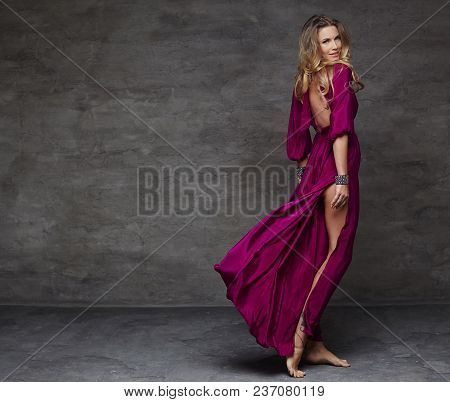 Blond Female In Long Red Dress In Motion. Studio Shoot.