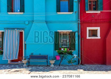 Small bench and bicycle in front of small houses painted in blue and red colors in Burano, Italy.