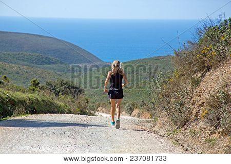 Sportive mature woman jogging down hill at the atlantic ocean
