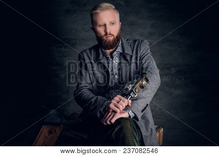 Portrait Of A Blond Bearded Male Holds Old Vintage 8mm Video Camera.