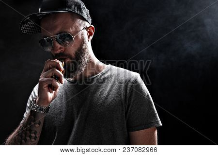 Pensive Black Bearded Male Dressed In A Grey Shirt, Sunglasses And Baseball Cap Vaping. Man In Holdi