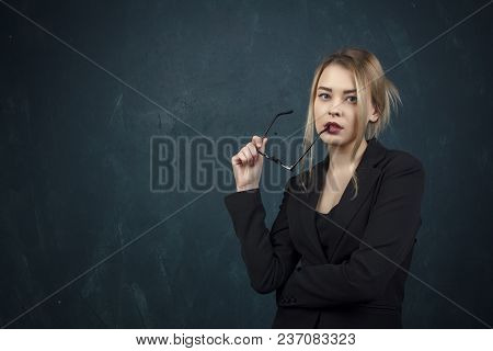 Portrait Of A Beautiful Woman With Sunglasses In Hands And Suit Against A Blue Textural Wall With Pl