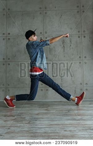 Teenage Boy In Jeans And Red Sweater, Denim Jacket And Baseball Cap Dances Hip-hop. Dynamics Of Mode