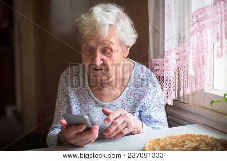 Elderly woman sits with a smartphone in her hands.