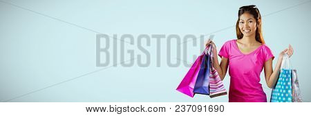 Shopper smiling with bags against light blue background
