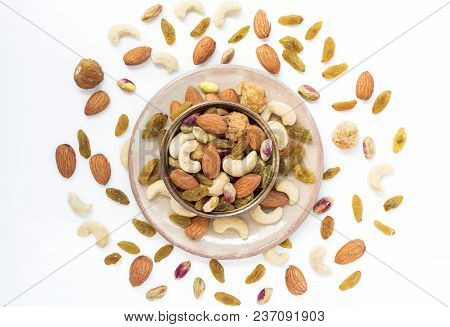 Dried Fruits And Variety Of Nuts In A Bowl On The White Table Background, Such As Figs, Almonds, Rai