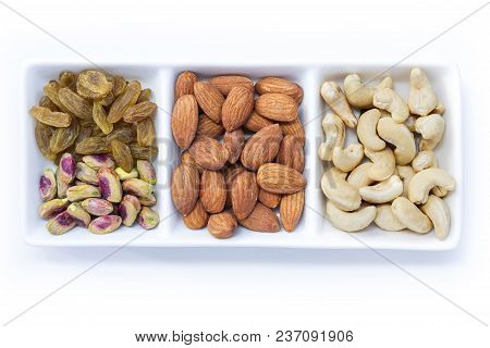 Dried Fruits And Variety Of Nuts In A Bowl On The White Table Background, Such As Almonds, Raisins,