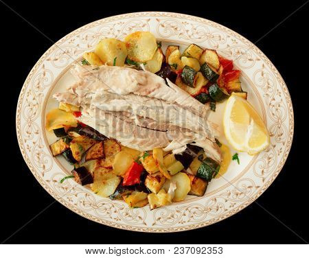 Fish fillet baked with vegetables, Italian dish in traditional plate isolated on black background