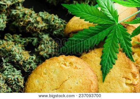 Cookies With Cannabis Leaves And Buds Of Marijuana On The Table. A Can Of Cannabis Buds Concept Of C