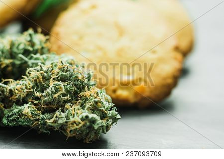 Cookies With Cannabis And Buds Of Marijuana On The Table. A Can Of Cannabis Buds Concept Of Cooking