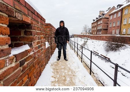 Man Standing On Brick Wall After Winter Storm In Warsaw, Poland