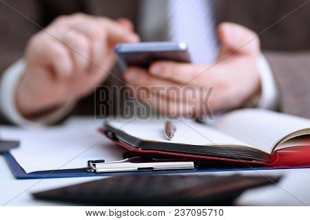 Male Arm In Suit Hold Phone And Silver Pen At Workplace Closeup. Read News Mania Send Sms Chat Addic