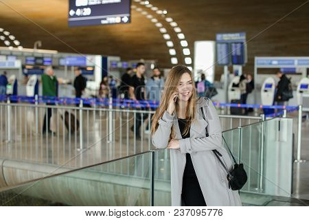 Smiling Businesswoman Talking By Smartphone At Airport Hall, Wearing Grey Coat And Bag. Concept Of C