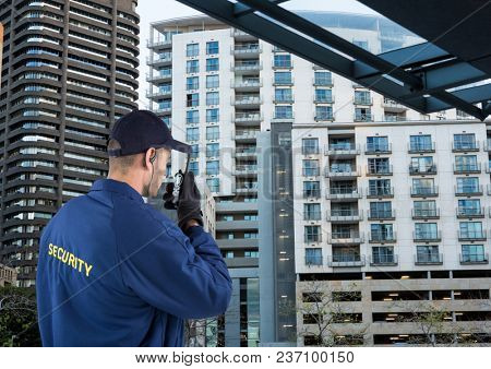 Digital composite of security guard speaking with walkie-talkie. City