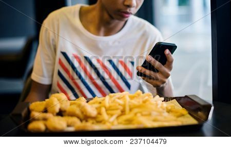 Close up of teenage boy using a smartphone eating french fries youth culture concept