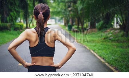 Back View Of Young Fitness Woman Running On The Road In The Morning, People And Sport Concept, Selec