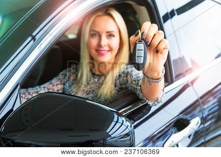 Happy Young Woman Driver Holding Auto Keys In Her New Modern Luxury Car With Selective Focus Effect