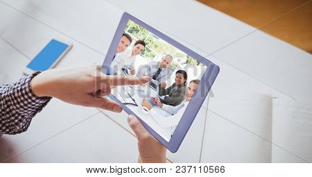 Digital composite of Hand touching tablet PC while video conferencing