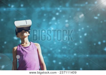 Girl in VR headset looking up against blue background with flares