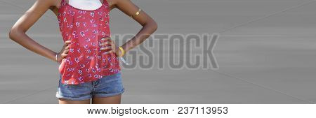 Millennial woman mid section with hands on hips against blurry grey background