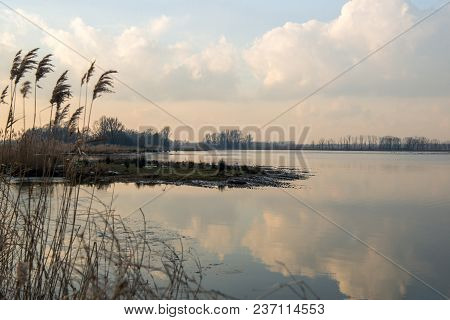 Blue Sky With White Clouds Reflected In The Mirror Smooth Water Surface Of A Flooded Part Of A Dutch