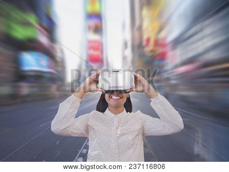 Happy woman in VR headset looking against city background