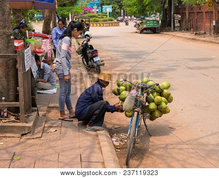 Siem Reap, Cambodia - 30 March, 2018: Coconut Seller On Bicycle. Simple Job Selling Coco Nuts. Stree
