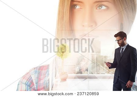 Handsome European Businessman Using Smartphone In Abstract Office Interior With Portrait And City Vi