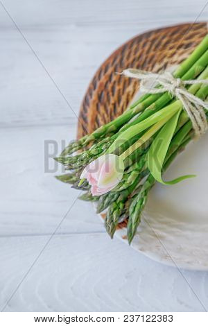 Green Asparagus And Pink Tulip On A White Wooden Background. Top View, Free Space